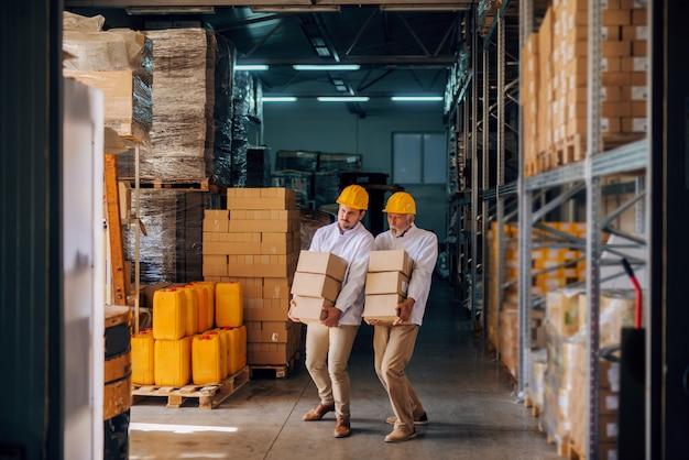 Colleghe che trasportano scatole con caschi sulle teste. interno di stoccaggio.