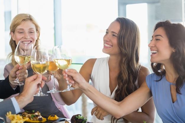 Colleghe felici che tostano i vetri di birra mentre pranzando