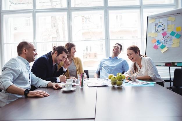Colleghi allegri che discutono nella sala riunioni