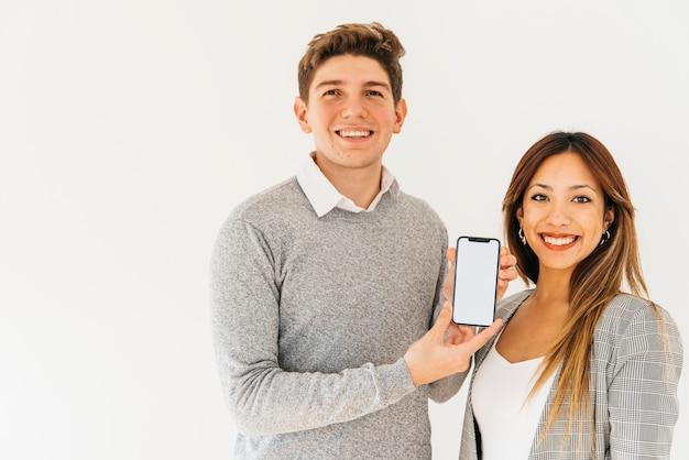 Colleghi allegri che presentano nuovo telefono
