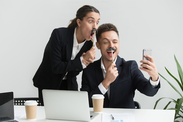 Colleghi che fanno autoritratto con accessorio baffi