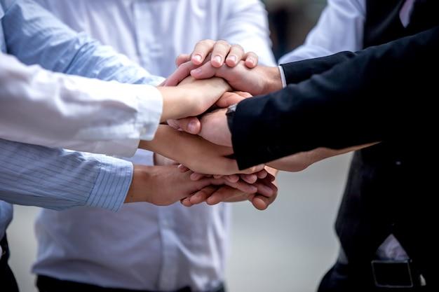 Colleghi che si mettono le mani l'uno sull'altro per il lavoro di gruppo durante l'attività