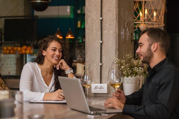 Colleghi che sprizzano tempo insieme, lavorando e bevendo un bicchiere di vino
