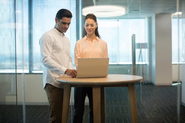 Colleghi che utilizzano computer portatile in ufficio moderno
