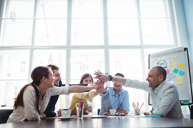 Colleghi con il cinque in sala riunioni