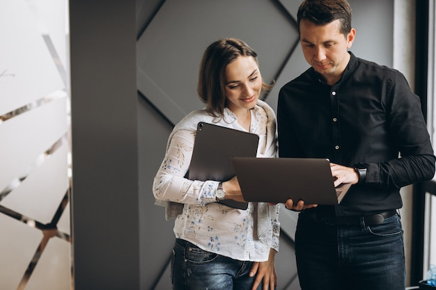 Colleghi dell'uomo di affari e della donna di affari che lavorano al computer portatile