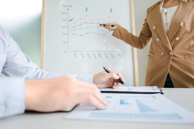 Colleghi di lavoro brainstorming discutendo le vendite valore prestazioni su bordo bianco, mentre la presentazione in sala ufficio moderna
