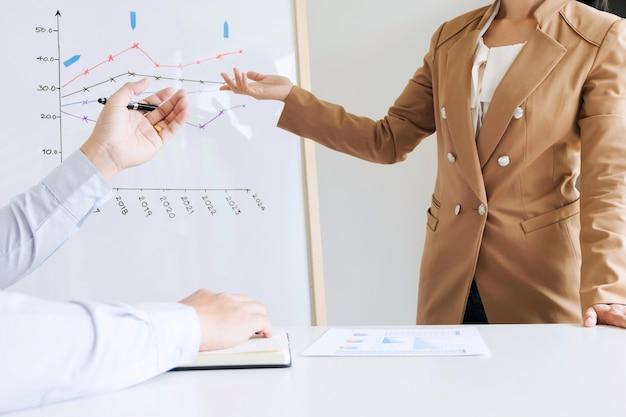 Colleghi di lavoro brainstorming discutendo performance di vendita su bordo bianco, mentre la presentazione in sala ufficio moderno