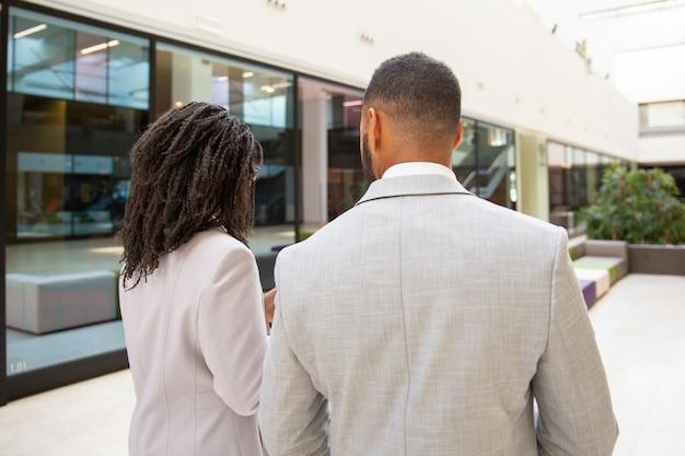 Colleghi di lavoro che discutono progetto mentre si cammina