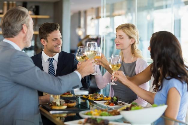 Colleghi di lavoro che tostano i bicchieri di birra mentre pranzano