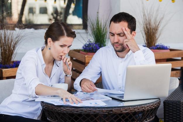 Colleghi di lavoro maschili e femminili che lavorano insieme su un problema difficile al caffè all'aperto. hanno un'espressione tesa sui loro volti