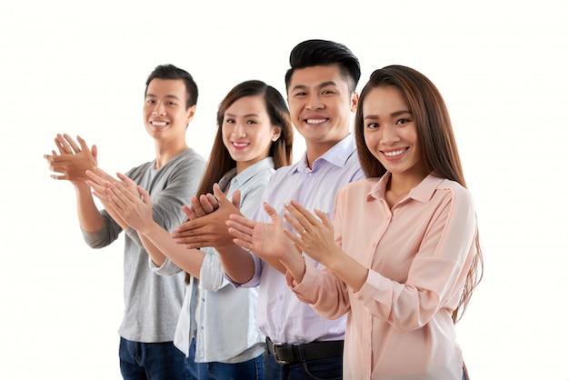 Colleghi di supporto che applaudono e guardano la fotocamera con gioia