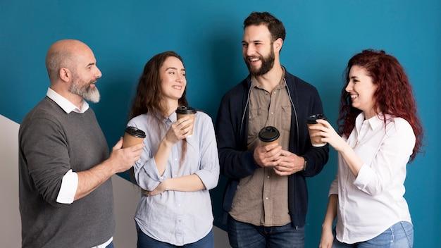 Colleghi di vista frontale che mangiano caffè insieme
