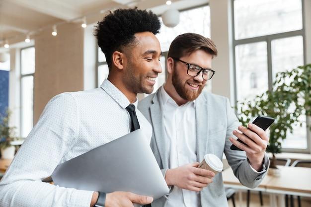 Colleghi felici degli uomini d'affari che parlano l'un l'altro