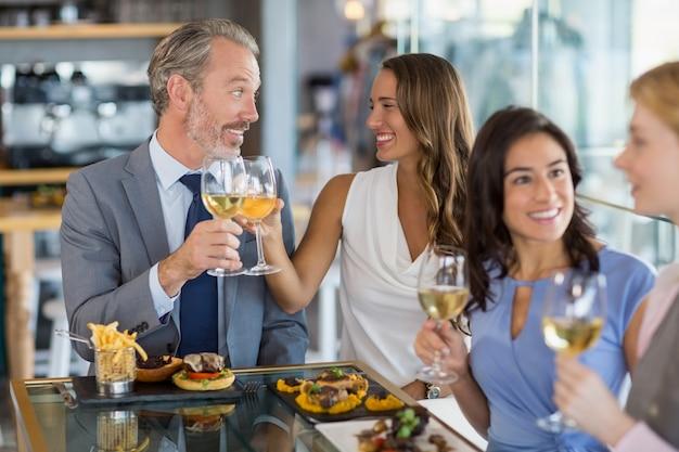 Colleghi felici di affari che interagiscono e che tostano i bicchieri di birra mentre pranzano