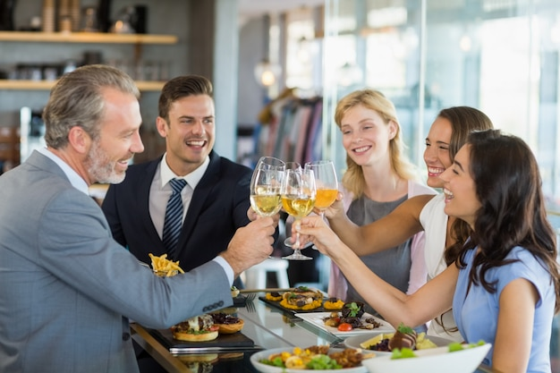 Colleghi felici di affari che tostano i bicchieri di birra mentre pranzano