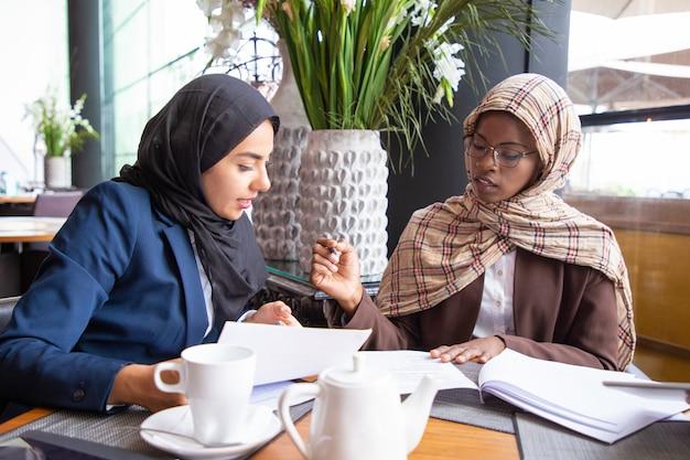 Colleghi femminili di affari che analizzano e che discutono i documenti