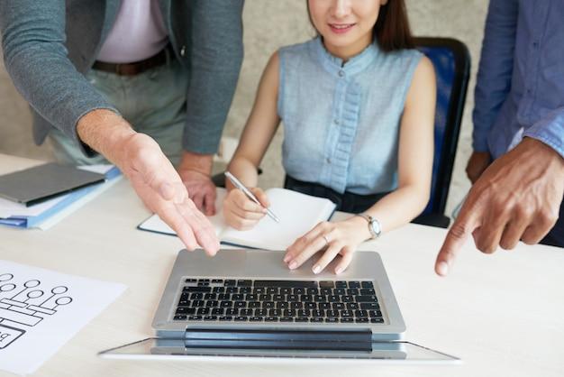 Colleghi irriconoscibili che esaminano e che indicano lo schermo del computer portatile alla riunione di lavoro