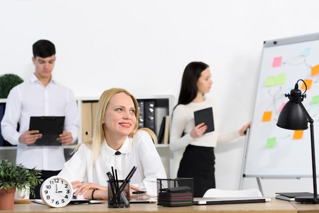 Colleghi maschii e femminili che stanno dietro la donna di affari sorridente che si siede nel luogo di lavoro