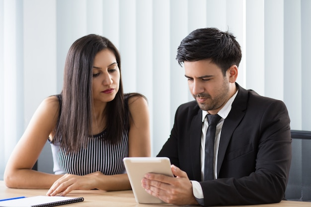Colleghi multietnici concentrati che osservano il rapporto online