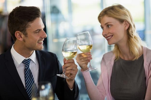 Colleghi sorridenti di affari che tostano il vetro di birra
