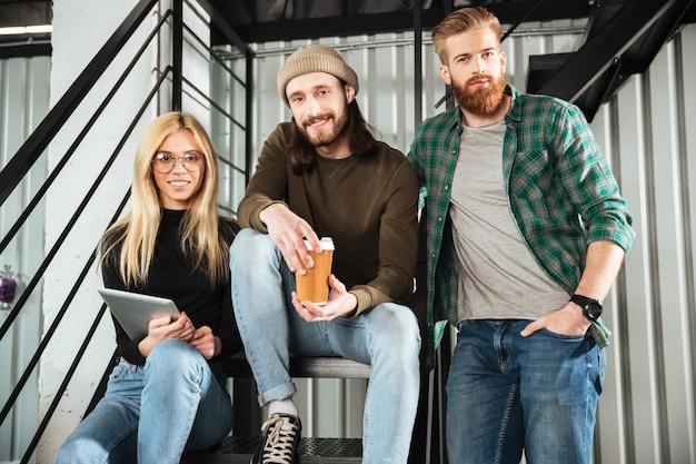 Colleghi sorridenti in ufficio che si siede sulla scala