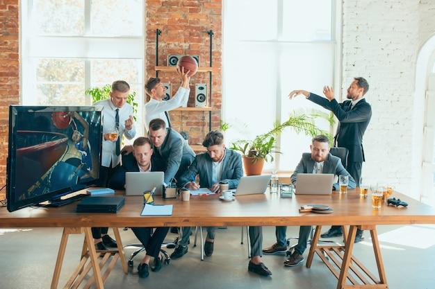Colleghi spensierati felici che si divertono in ufficio mentre i loro colleghi lavorano sodo e altamente concentrati.