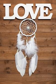 Collettore di sogno bianco e testo di amore sulla tavola di legno, disposizione piana