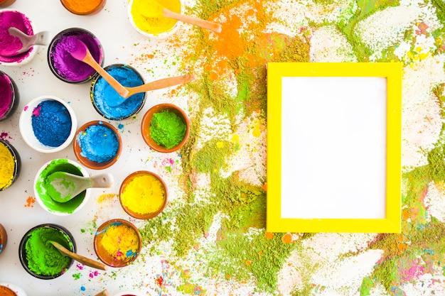 Collezione di ciotole con colori secchi brillanti vicino a telaio e pile di colori