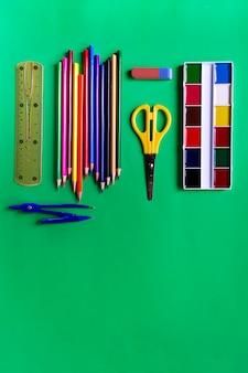 Collezione di materiale scolastico da vernici, matite, forbici, righello, cancellino e bussole su verde