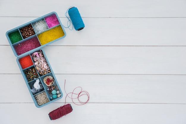 Collezione di perline in custodia blu con bobina di filato blu e viola brillante sulla scrivania bianca