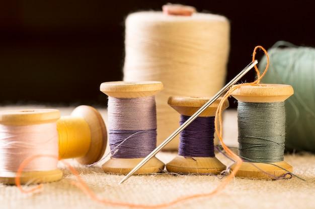 Collezione di rocchetti di filo colorato con ago
