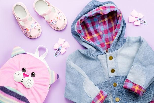 Collezione di vestiti per bambina con giacca di jeans, sandali, zaino su pastello
