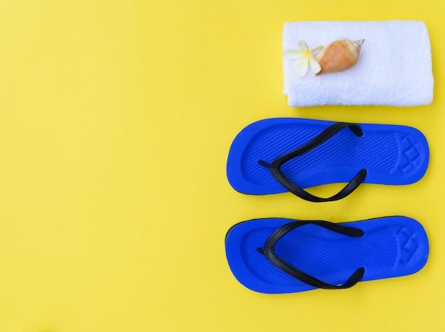 Collezione estiva, conchiglia piatta, pantofole blu, asciugamano bianco e fiori di frangipane su sfondo giallo