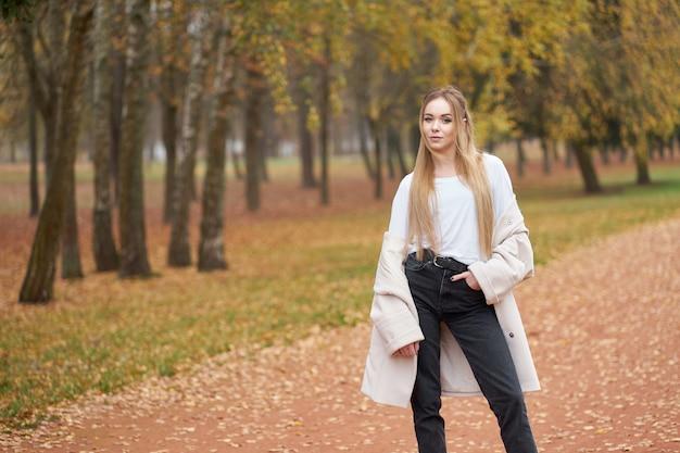 Collezione street moderna. giovane ragazza bionda sicura che indossa camicia bianca, jeans neri e cappotto autunnale alla moda