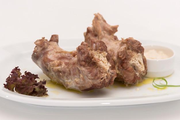 Colli di tacchino, serviti con purea di rafano, disposti su piatto bianco, sfondo chiaro