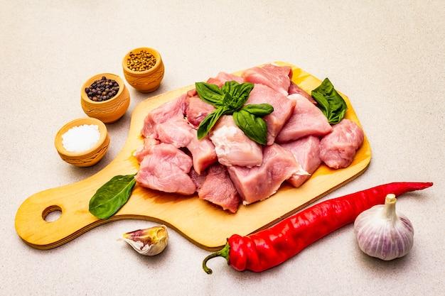 Collo di maiale crudo, tagliato a pezzi con verdure fresche e spezie secche