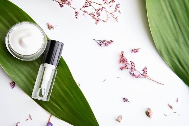 Collocato bottiglia di crema bianca, pacchetto di etichetta vuota per mock up su uno sfondo verde fogliame e fiori