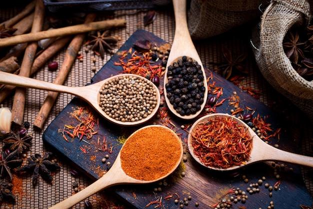 Coloful varie spezie ed erbe in cucchiaio di legno sul piatto di legno di texture naturale.