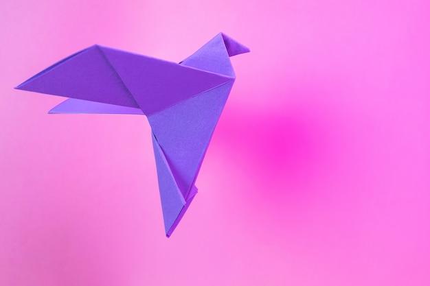 Colombe viola di carta origami su un rosa pastello