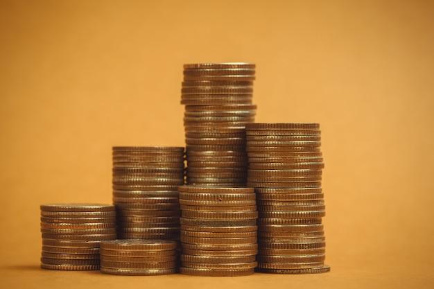 Colonne di monete, mucchi di monete su sfondo marrone