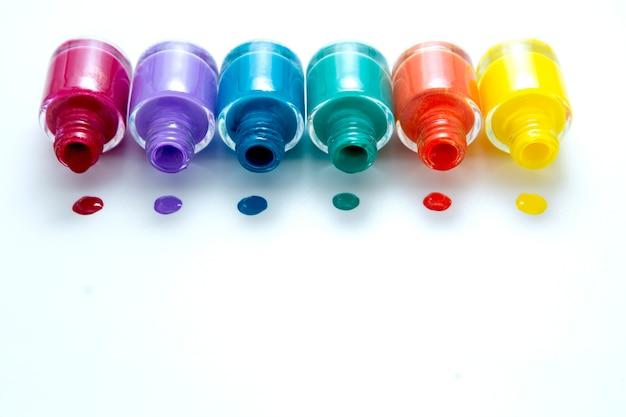 Colorate bottiglie di smalto su bianco, copia dello spazio