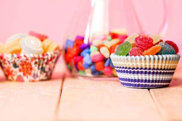 Colorato molti dolci gelatina, sapore di frutta, compleanno dolce caramelle a forma di cuore con sfondo rosa pastello