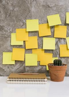 Colorato post-it, taccuino memo, matita, cactus in vaso di fiori sulla scrivania bianca sullo sfondo di cemento, concetto di spazio di lavoro