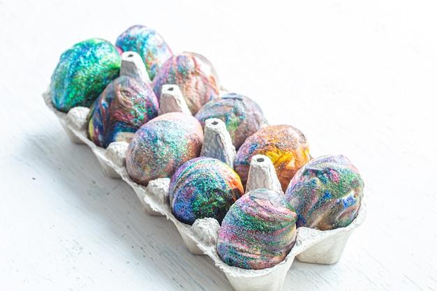 Colorazione cosmica di uova di pasqua su uno sfondo chiaro.