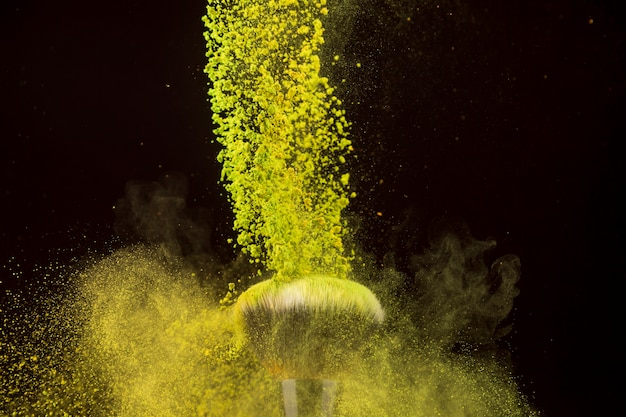 Colore a cascata in polvere che cade sulla spazzola di fondazione