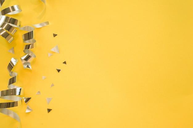 Colore argento del nastro rotolante e coriandoli su sfondo giallo
