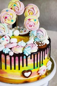 Colore dell'arcobaleno della torta dei bambini su un bianco con meringa di legno