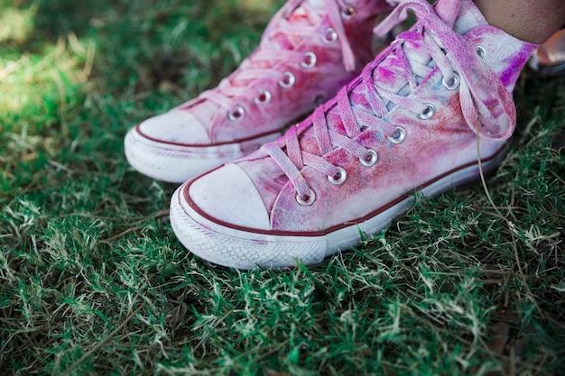 Colore holi sopra le scarpe di tela bianca sull'erba verde