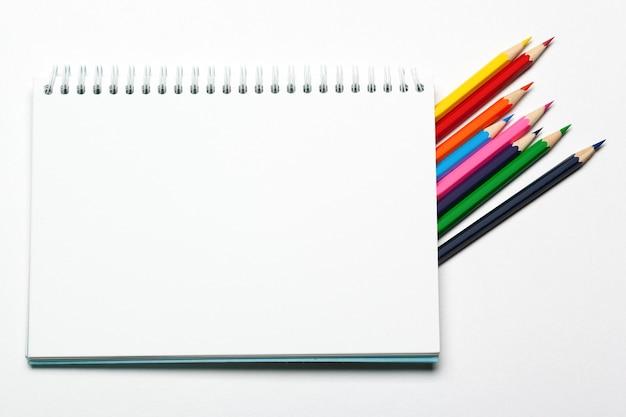 Colore in bianco della matita e del blocco note su un blackground della tavola